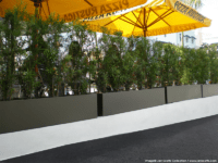 Line of black rectangular planters edging an eating area