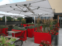 Outdoor eating area with red planters between tables