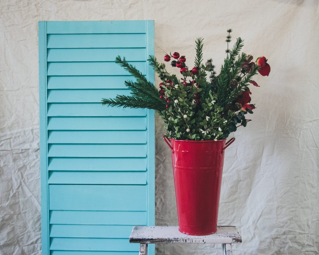 Pine branches and red berries make this red planter pop